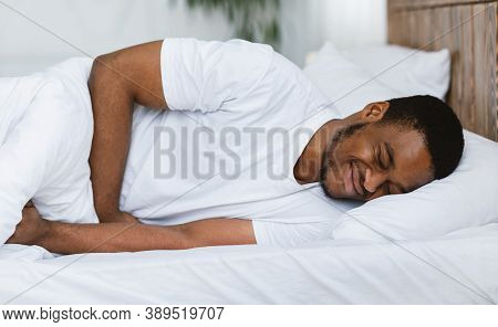 Stomachache. African American Man Suffering Abdominal Pain Touching Aching Stomach Lying In Bed At H