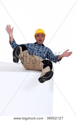 Average worker lying on top of a white base