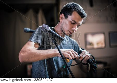 Theater Audio Technician Adjusting An Microphones On The Scene