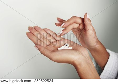 Young Woman Distributes Hand Cream On Her Hands. The Concept Of Skin Hydration, Hand Care And Wrinkl