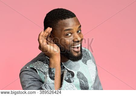 Curious Interested African-american Man Holding Hand Near Ear And Trying To Hear Information, Pink S
