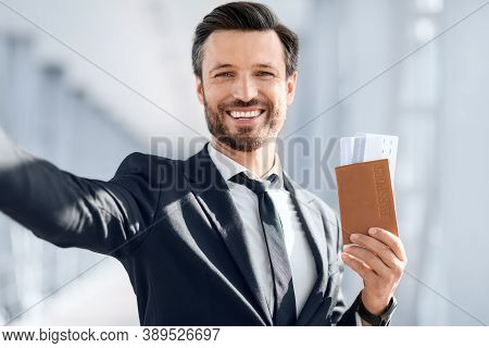 Cheerful Middle-aged Businessman Taking Selfie Before Departure, Showing Passport With Flight Ticket