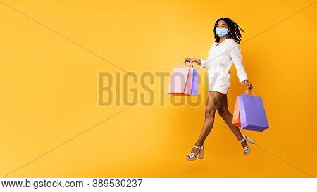 Safe Shopping. Black Woman In Medical Face Mask Running In Mid-air Carrying Colorful Shopper Bags Po