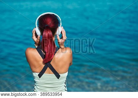 Woman Posing With Back Wearing White Headset. Female Enjoying Ocean View. Contemplation And Meditati