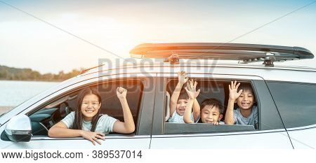 Happy Kids Travel By The Car, Little Boy Peeks Out Of The Car In The Sunset. Happy Siblings Waving H