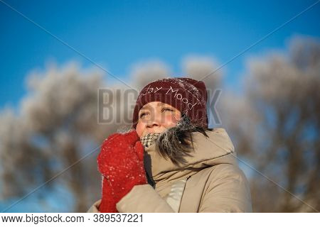 Happy Young Woman In Red Winter Hat And Red Mittens On The Snow Sunny Day Against Blue Sky