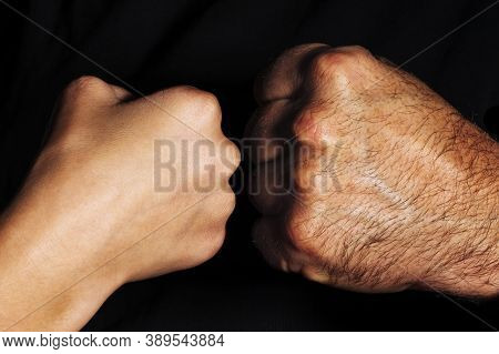 Female Fist Against Male Fist. Punch Is A Severe And Agressive Opposition. Opposite Direction. The C