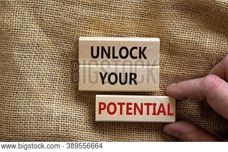Male Hand Placing A Block With Word 'potential' On Blocks Tower With Words 'unlock Your Potential'.