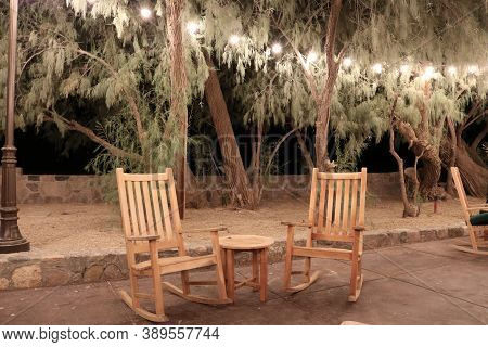 Hanging Lights Above An Outdoor Patio With Modern Wooden Chairs Besides A Table Surrounded By Manicu