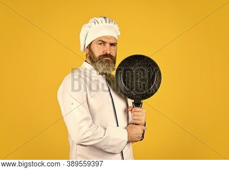 Nonstick Cookware. Frying Without Oil. Professional Kitchenware. Bearded Chef Preparing Breakfast. N