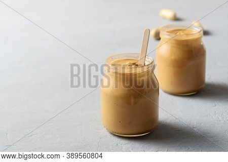 Homemade Peanut Butter In Glass Jars On Concrete Surface.