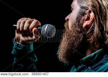 Male Singing With A Microphones. Man With A Beard Holding A Microphone And Singing. Bearded Man In K