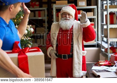 Happy Old Bearded Santa Claus Waving Hand To Courier Delivering Christmas Present Parcel On Xmas Eve