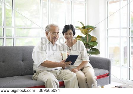 A Happy Senior Asian Couple Is Using Tablet And Talking With Family On Webcam At Home, Retirement Co