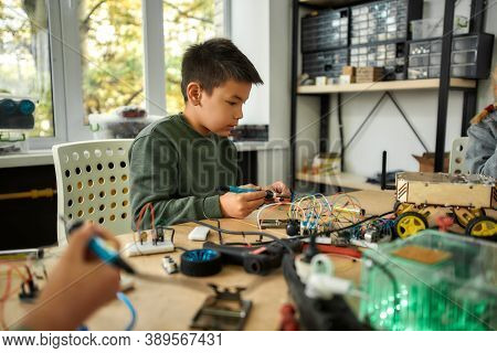 Young Engineer Using Soldering Iron To Join Chips And Wires. Robotics And Software Engineering For E