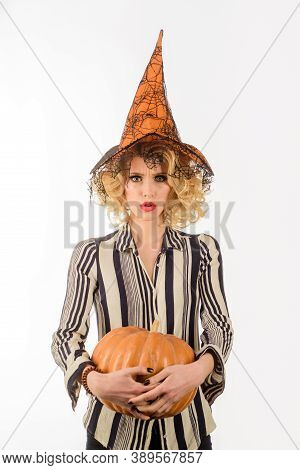 Preparation Halloween Holidays. Serious Girl In Witch Hat With Pumpkin. Pretty Woman In Witch Hallow