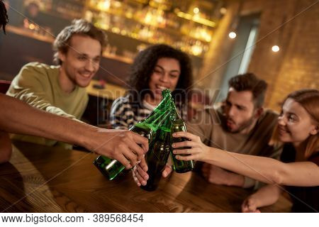 Cheers. Group Of Friends In The Bar Watching Sports Match On Tv Together, Drinking Beer, Clinking Bo