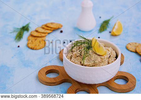 Appetizer, Fish Pate From Mackerel, Boiled Eggs And Onions In A White Ceramic Bowl On A Blue Concret