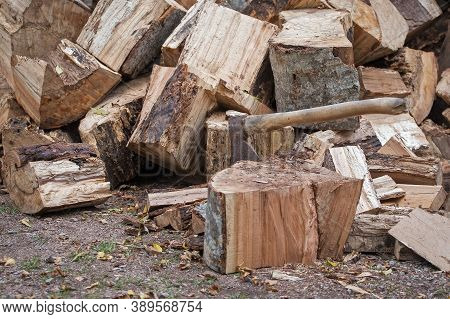 Preparation Of Firewood For The Winter. Chopped Wood Trunks For Winter Fireplace Heating. Metal Axe