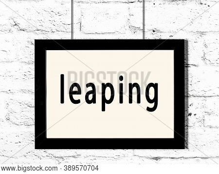 Black Wooden Frame With Inscription Leaping Hanging On White Brick Wall