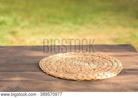 Round Wicker Napkin For Cutlery On A Wooden Table Against The Background Of Autumn Nature. Texture T