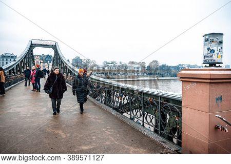 Frankfurt, Germany - January 22, 2019: River view of The Eiserner Steg. The Eiserner Steg is a pedestrian bridge in Frankfurt am Main built in 1868. City skyline in Frankfurt, Germany.