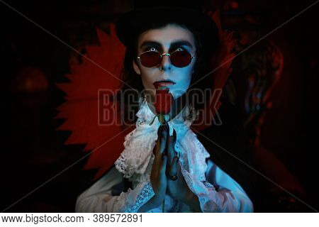 Portrait of a romantic vampire aristocrat of the 19th century holding a rose in his hand. Halloween.