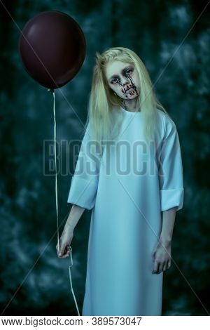 Portrait of a scary pale girl from a horror film in the forest with a baloon. Zombie, halloween.