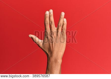 Hand of hispanic man over red isolated background greeting doing vulcan salute, showing back of the hand and fingers, freak culture
