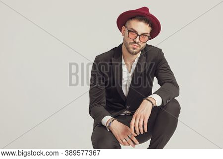 Serious fashion model wearing sunglasses and hat while crouching on gray studio background