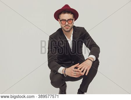 Confident fashion model holding hands together, wearing sunglasses and hat while crouching on gray studio background