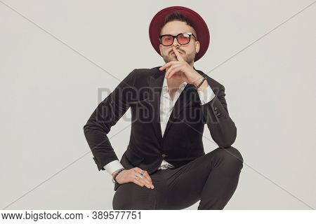 Charming fashion model gesturing silence and smiling, wearing sunglasses and hat while crouching on gray studio background