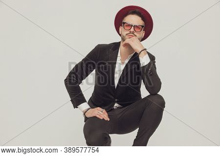 Suspicious fashion model holding hand on chin, wearing sunglasses and hat while crouching on gray studio background