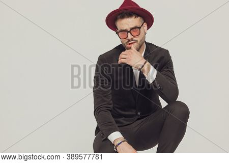 Charming fashion model touching his lips, wearing sunglasses and hat while crouching on gray studio background