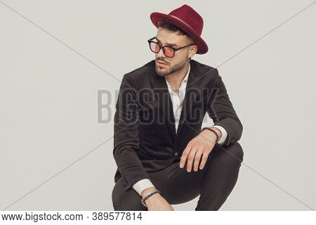 Eager fashion model looking away, wearing sunglasses and hat while crouching on gray studio background