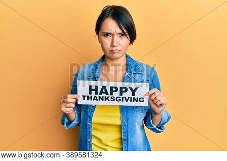 Beautiful young woman with short hair holding happy thanksgiving message paper skeptic and nervous, frowning upset because of problem. negative person.