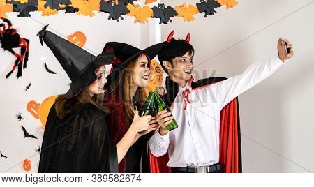 Group of friends asian young adult people celebrate a Halloween party carnival Festival. They wear Halloween costumes take selfie photographing. Halloween celebrate and international holiday concept.