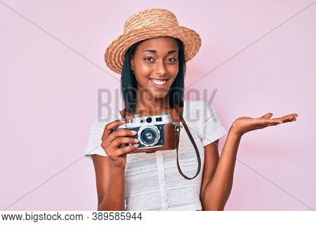 Young african american woman wearing summer hat holding vintage camera smiling cheerful presenting and pointing with palm of hand looking at the camera.
