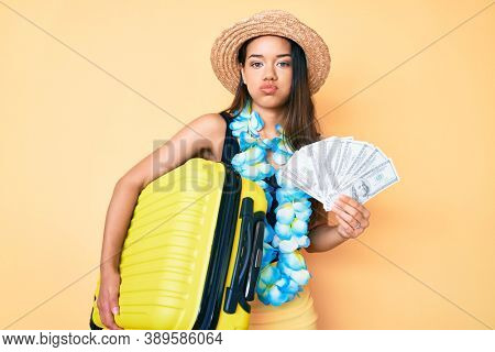 Young beautiful latin girl wearing hawaiian lei holding cabin bag and dollars banknotes puffing cheeks with funny face. mouth inflated with air, catching air.