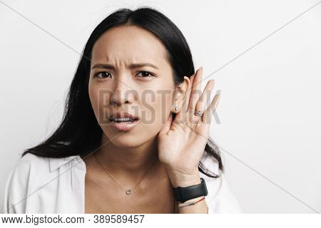 Displeased asian woman overhearing while posing at camera isolated over white background