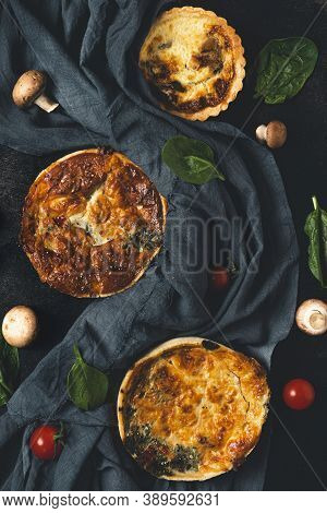 Still Life With Homemade Pies Quiche Lorraine, Dark Textile, Spinach, Tomatoes And Mushrooms On Blac