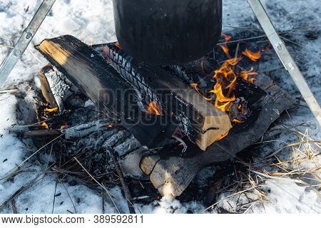 Closeup Campfire In The Snow And Caked Pot In Soot Over The Fire On Tripod, Winter Outdoor Cooking A