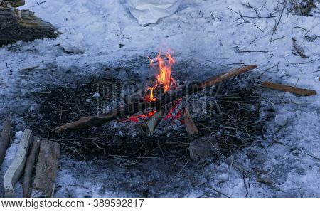 Small Campfire And Hot Embers Is Burning Low In The Snow At Dusk, Winter Fire And Chopped Firewood A