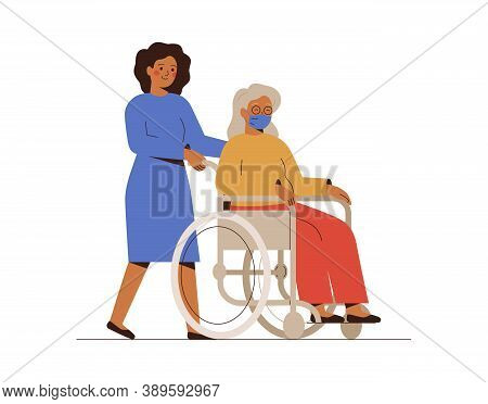 Nurse Or Social Worker Helps The Elderly Disabled Patient And Drives Her In A Wheelchair. A Young Fe