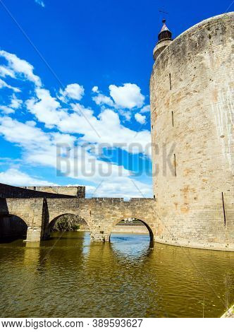 Powerful walls and a moat with water surround the ancient city of Aigues-Mortes. Mediterranean coast of France. The historical tower of Constance. The concept of historical  tourism
