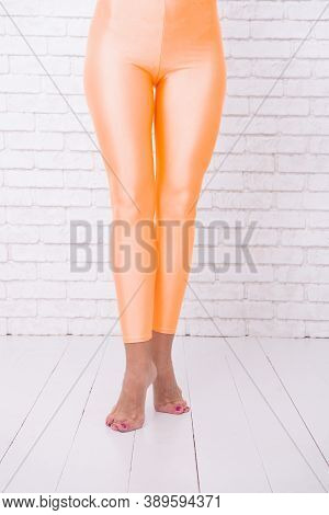 Sport Wear Fashion. Orange. Practicing In Ballet Studio. Woman In Orange Leggings On Legs. Dancing B