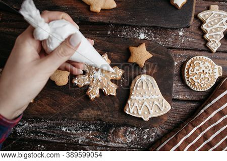 Christmas Bakery. Decorating Freshly Baked Gingerbread Cookies With Icing, View From Above. Festive