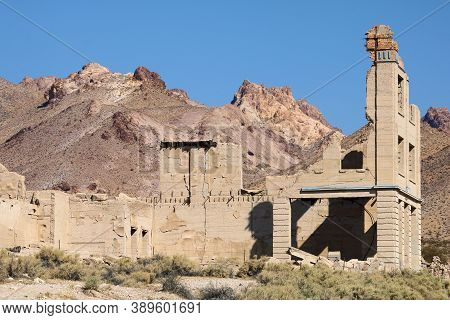 Abandoned Collapsed Building On An Arid Plain With Barren Mountains Beyond Taken At The Mojave Deser
