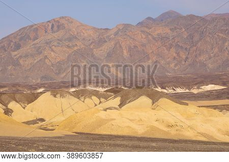 Eroded Hills On An Arid Plateau With Barren Mountains Beyond Taken In Death Valley, Ca