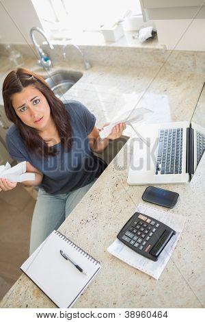 Woman feeling financial pressure in kitchen